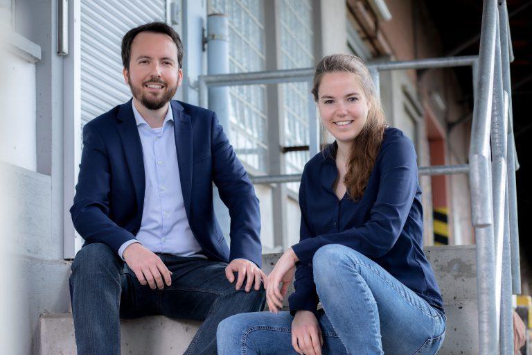Christian Pollack und Carolin Schröer sind das Team von mein DIGITALreferent und sitzen auf einer Treppe mit Stahlgeländer