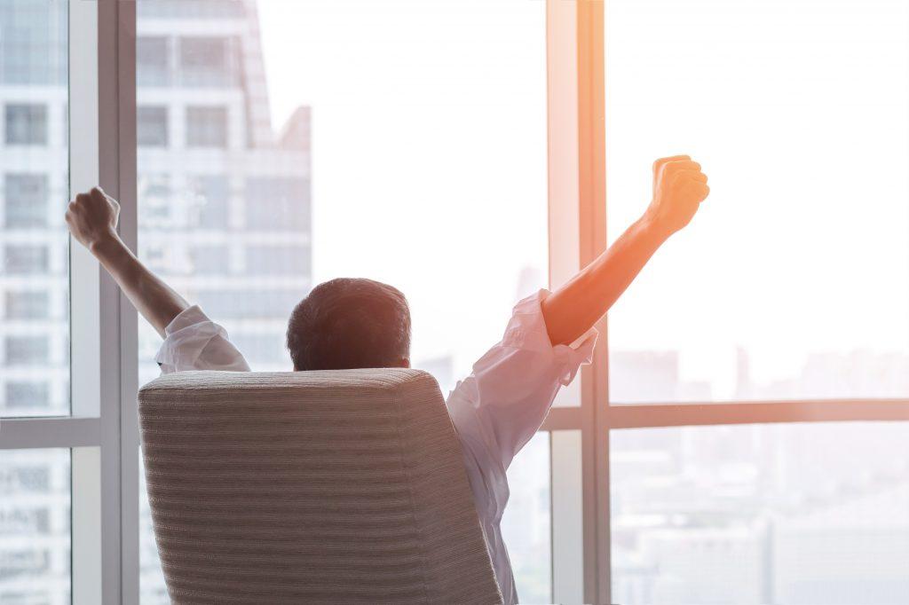Ein Mann sitzt im Schreibtischstuhl mit dem Rücken zum Betrachter und streckt die Arme in die Höhe und schaut aus dem großen Glasfenster