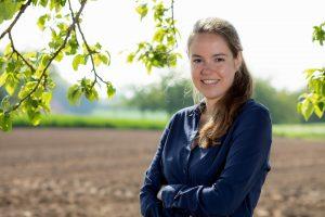 Carolin Schröer von mein DIGITALreferent steht mit verschränkten Armen in der Natur im Schwarzwald und möchte den öffentlichen Dienst in der Personalgewinnung unterstützen